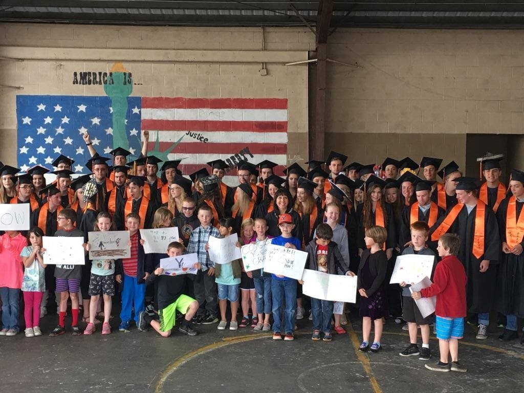The class of 2017 pose for a photo with elementary school students after parading through the YCES building Friday.