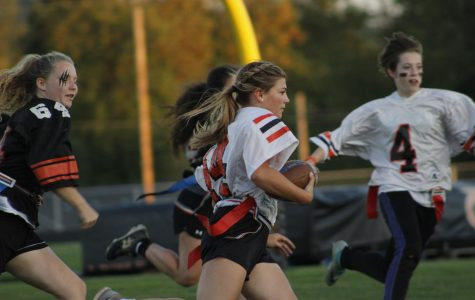 Sophomores and seniors run with the ball in this Powder Puff game.  Seniors won this year's game. Photo by Lajla Raske