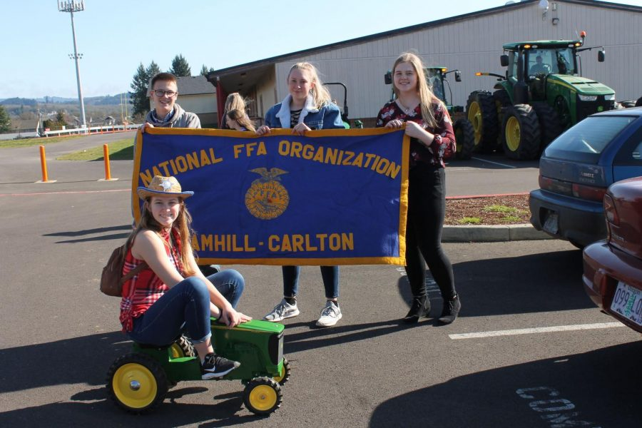 Students+Alex+Puig%2C+Claire+Lapp%2C+and+Zoe+Lehman+hold+a+YC+FFA+banner.+In+front+of+the+banner+sits+Freshman+Izzy+Hoffarth+on+a+tricycle+style+tractor.+Photo+by+Lajla+Raske+