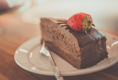 A chocolate cake with a fudge-like topping sits on a small white plate.  According to a study published in a 2019 article at Perishablenews.com, chocolate cake is the most popular searched cake online with over 394,000 search results each month worldwide.