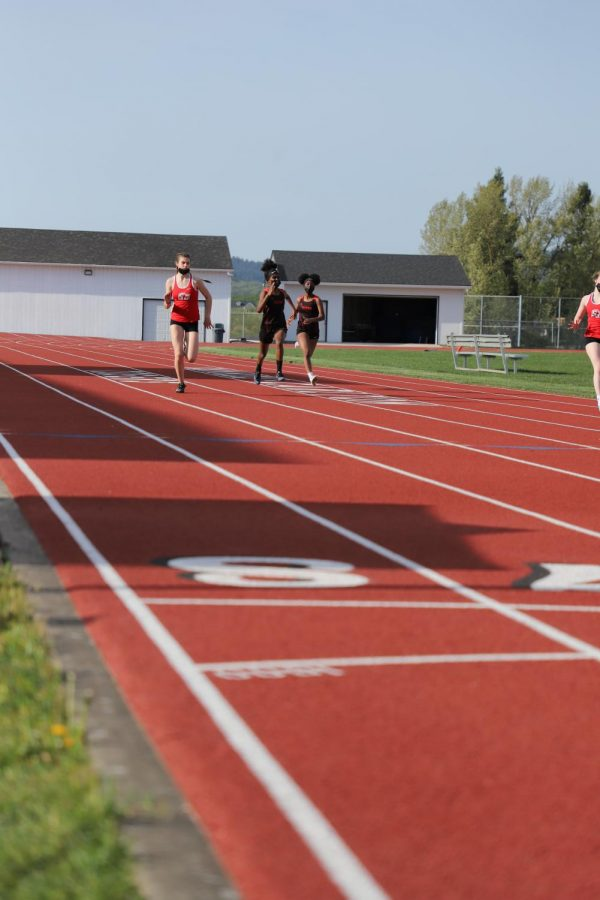 Some track athletes practicing on the track.